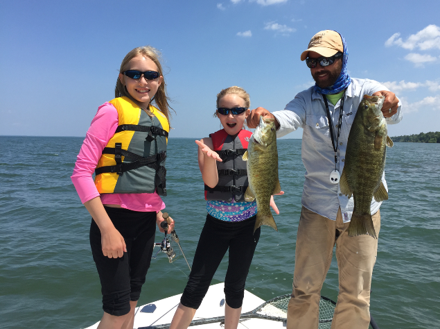 "Chicagoans Meredith and Claire had some good fun on Chequamegon Bay this week catching smallmouth and enjoying some beach time out at Long Island. ""Hard to ignore swimming when the water is 75 degrees,"" said their guide, Luke Kavajecz of Ashland's Anglers All. ""It was a fun day for sure!"" (Photo courtesy of Luke Kavajecz)"